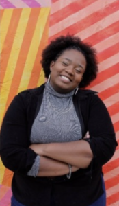 Shaddai stands smiling in front of a colorful background.