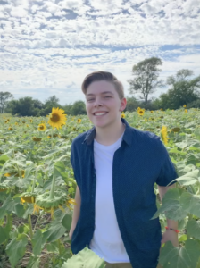 River stands smiling in a sunflower field.
